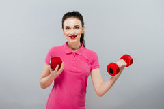 Młody Azjatycki kobiety szkolenie mięśniowy i jabłko ręka z czerwonymi dumbbells, kg Obraz Stock