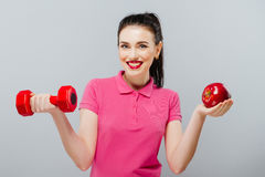 Młody Azjatycki kobiety szkolenie mięśniowy i jabłko ręka z czerwonymi dumbbells, kg Obrazy Stock