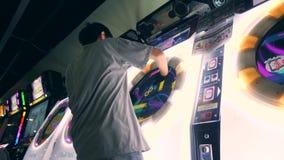 Młody Azjatycki mężczyzna Bawić się arkada Maszynowego bębenu Muzyczną grę i Pcha Jaskrawych kontrolerów guziki 4K Gemowa strefa  zbiory