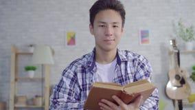 Młody Azjatycki mężczyzna czyta książkę w żywym pokoju i patrzeje kamerę zbiory wideo