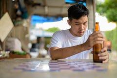 Młody Azjatycki mężczyzna dostaje pijący w ulicach outdoors zdjęcia stock
