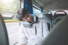 Młody Azjatycki mężczyzna podróżnika obsiadanie na autobusie i dosypianie z poduszki, transportu, turystyki i wycieczki samochodo fotografia royalty free