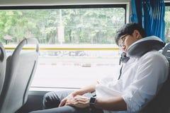 Młody Azjatycki mężczyzna podróżnika obsiadanie na autobusie i dosypianie z poduszki, transportu, turystyki i wycieczki samochodo obrazy stock