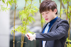 Młody Azjatycki męski dyrektor wykonawczy patrzeje czas Obrazy Royalty Free