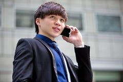 Młody Azjatycki męski dyrektor wykonawczy używa mądrze telefon Obraz Royalty Free