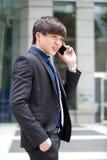 Młody Azjatycki męski dyrektor wykonawczy używa mądrze telefon Obrazy Stock