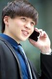Młody Azjatycki męski dyrektor wykonawczy używa mądrze telefon Zdjęcie Royalty Free