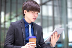 Młody Azjatycki męski dyrektor wykonawczy używa pastylka peceta Zdjęcie Royalty Free
