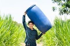 Młody Azjatycki rolnik niesie błękitne wody zbiornika zdjęcia royalty free