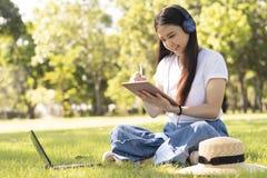 Młody Azjatycki waman jest pisze puszku na pastylce podczas bierze czas relaks w parku obrazy stock