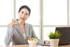 Młody azjatykci bizneswoman cieszy się zdrowej sałatki Fotografia Stock