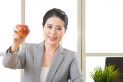 Młody azjatykci bizneswoman je zdrową przekąskę, jabłko Zdjęcie Royalty Free