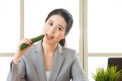 Młody azjatykci bizneswoman je zdrową przekąskę, ogórek Zdjęcie Royalty Free