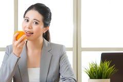 Młody azjatykci bizneswoman je zdrową przekąskę, pomarańcze Zdjęcie Stock