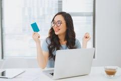 Młody azjatykci bizneswoman używa kredytową kartę dla linii zapłaty Zdjęcie Royalty Free