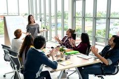 Młody azjatykci bizneswoman wyjaśnia pomysł grupa kreatywnie różnorodna drużyna przy nowożytnym biurem zdjęcie stock