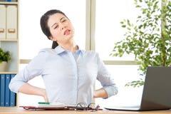 Młody azjatykci bizneswoman z bólem w plecy obrazy stock