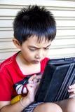 Młody azjatykci chłopiec use pastylka. Zdjęcie Stock