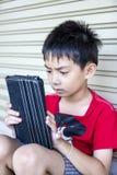 Młody azjatykci chłopiec use pastylka. Obrazy Stock