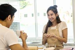 Młody azjatykci damy pęknięcie r, jajko w puchar wypełniał z mąką Fotografia Royalty Free