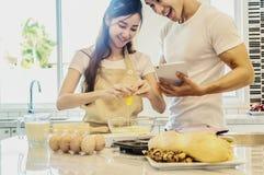 Młody azjatykci damy pęknięcie r, jajko w puchar wypełniał z mąką Zdjęcie Royalty Free