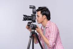 Młody azjatykci fotograf trzyma cyfrową kamerę, podczas gdy pracujący i Fotografia Stock
