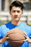 Młody azjatykci gracz koszykówki trzyma piłkę Zdjęcia Royalty Free