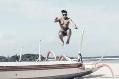 Młody azjatykci indonezyjski mężczyzna ma zabawę na plaży tropikalna Bali wyspa, Indonezja Obraz Stock