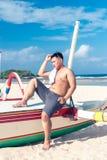 Młody azjatykci indonezyjski mężczyzna relaksuje na plaży tropikalna Bali wyspa, Indonezja Zdjęcie Stock