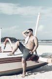 Młody azjatykci indonezyjski mężczyzna relaksuje na plaży tropikalna Bali wyspa, Indonezja Obraz Stock
