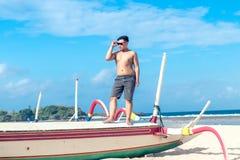 Młody azjatykci indonezyjski mężczyzna relaksuje na plaży tropikalna Bali wyspa, Indonezja Fotografia Royalty Free