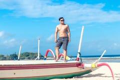 Młody azjatykci indonezyjski mężczyzna relaksuje na plaży tropikalna Bali wyspa, Indonezja Zdjęcia Stock