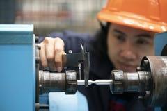 Młody azjatykci kobieta inżynier używa noniusz dla miary próbny kawałek zdjęcia stock