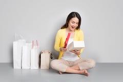 Młody azjatykci kobiety obsiadanie oprócz rzędu torba na zakupy trzyma r Obraz Stock