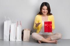 Młody azjatykci kobiety obsiadanie oprócz rzędu torba na zakupy trzyma r Obrazy Stock