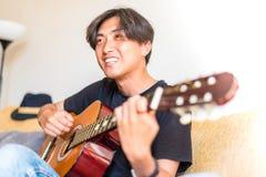 Młody azjatykci mężczyzna bawić się hiszpańską gitarę indoors obraz stock