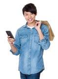 Młody azjatykci mężczyzna chwyt z torba na zakupy i pastylki komputerem osobistym Obrazy Royalty Free
