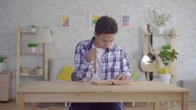 Młody azjatykci mężczyzna czyta biblię z różanem w jego ręce zbiory