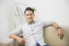 Młody azjatykci mężczyzna obsiadanie na kanapie i patrzeć kamerę fotografia stock