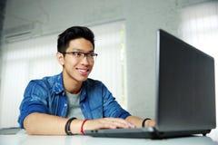 Młody azjatykci mężczyzna pracuje przy biurem Fotografia Stock