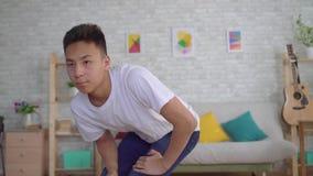 Młody azjatykci mężczyzna robi rozgrzewce na macie zbiory