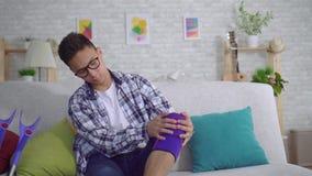 Młody azjatykci mężczyzny obsiadanie na leżance stawia naciągowego elastycznego bandaż na chorym kolanie zamkniętym w górę zdjęcie wideo