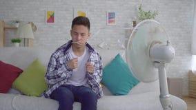 Młody azjatykci mężczyzny obsiadanie przed pracującym fan pojęcie upał zbiory wideo