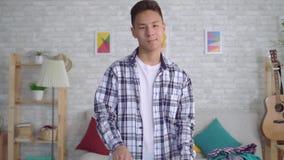 Młody azjatykci mężczyzny prasowanie odziewa na prasowanie desce patrzeje ono uśmiecha się i kamerę zbiory