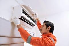 Młody azjatykci męski technika naprawiania powietrza conditioner z śrubą Obraz Royalty Free