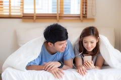 Młody azjatykci para uśmiech słucha muzykę z mądrze telefonem komórkowym na łóżku przy sypialnią z zabawą i cieszy się zdjęcie stock