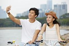 Młody azjatykci pary jazdy rower i brać selfie Obrazy Royalty Free