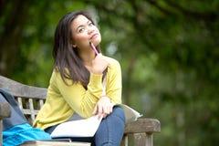 Młody azjatykci studenta uniwersytetu obsiadanie na drewnianej ławce w parku Obraz Royalty Free
