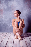 Młody baleriny obsiadanie na drewnianej podłoga zdjęcia stock