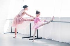 młody baletniczy nauczyciel patrzeje małego studenckiego rozciąganie zdjęcie royalty free